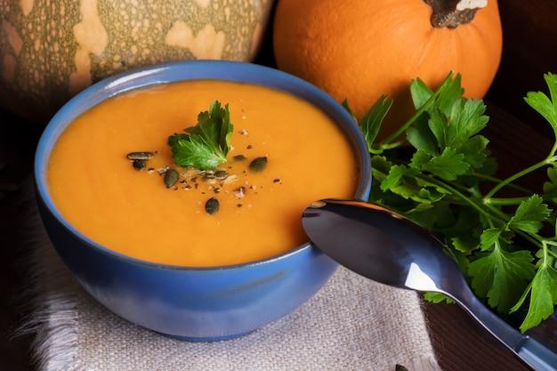 Kürbissuppe in einer schüssel serviert mit petersilie, olivenöl und kürbiskernen