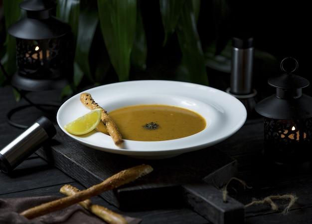 Kürbissuppe in hühnerbrühe mit zimtstangen und zitronenscheiben