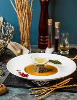 Kürbissuppe mit mittelstück und zitronenscheibe