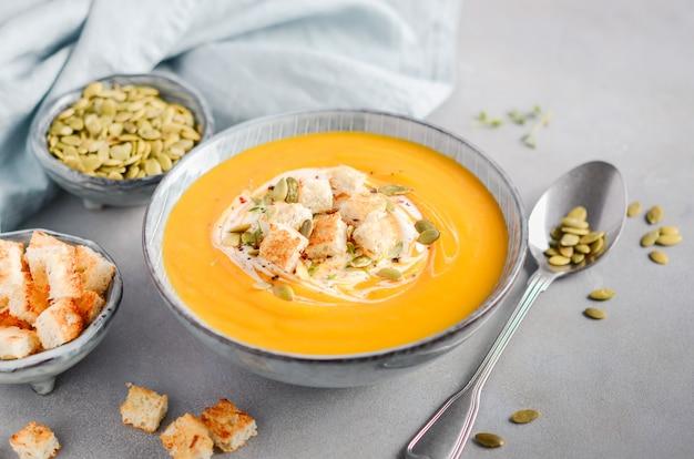 Kürbissuppe mit sahne, croutons, kürbiskernen und thymian auf grauem beton oder stein
