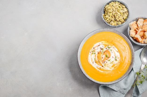 Kürbissuppe mit sahne, croutons, kürbiskernen und thymian