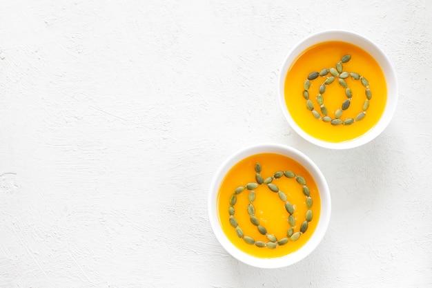 Kürbissuppe mit samen auf einem weißen holz