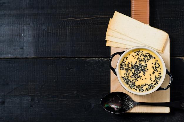 Kürbissuppe mit schwarzem sesam und crackern.