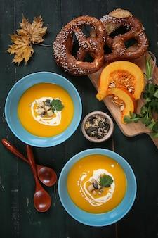Kürbissuppe. saisonale gerichte. suppe mit kürbisblättern und brezeln dekoriert. herbst