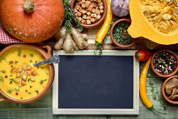 Kürbissuppenhintergrund mit leerer tafel nahe bei einer schüssel suppe und gesunden suppenbestandteilen