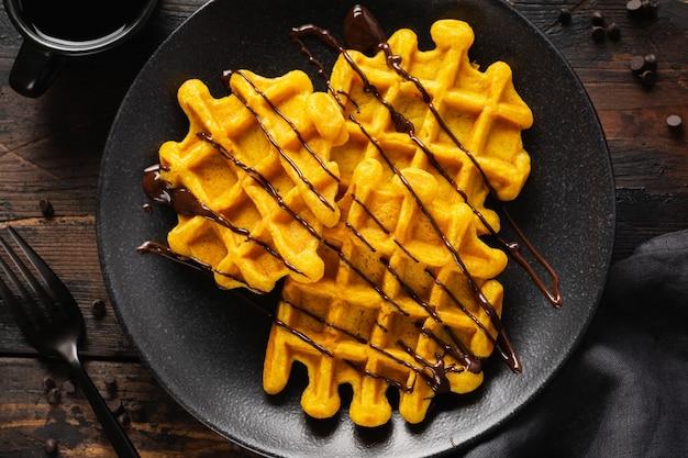 Kürbiswaffeln mit schokolade und zuckerpulver auf dunklem altem