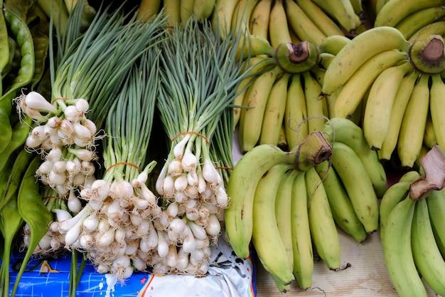 Kürzlich geerntete frühlingszwiebeln und bündelbanane bereit, am markt zu verkaufen