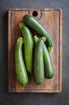 Kürzlich geerntete zucchini, grünes gemüse auf dunkelheit
