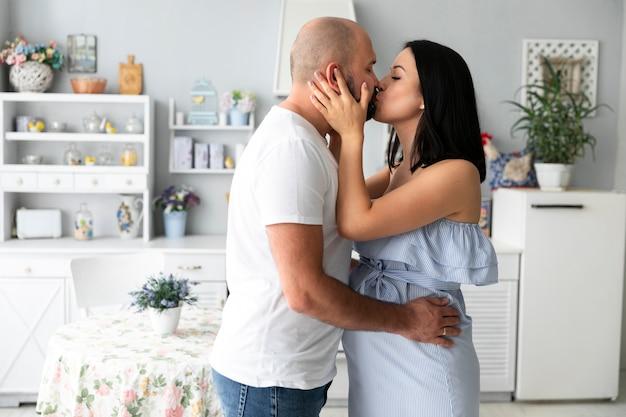 Küssen des ehemanns und der schwangeren frau des mittleren schusses
