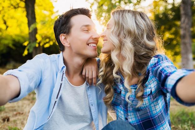 Küssen des jungen stilvollen paares, das im park, glückliche familie des mannes und der frau zusammen sitzt