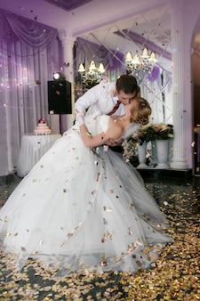 Küssen sie und tanzen sie junge braut und bräutigam im bankettsaal