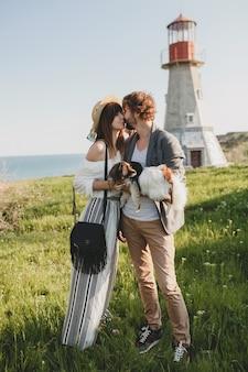 Küssen stilvolles hipster-paar in der liebe, die mit hund in der landschaft geht