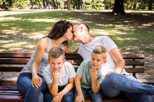 Küssende eltern und kinder, welche die kamera betrachten