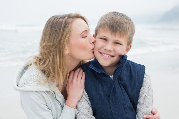 Küssender junge der mutter am strand