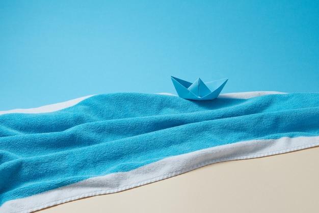 Küste aus flauschigem strandtuch und handgemachtem papierboot