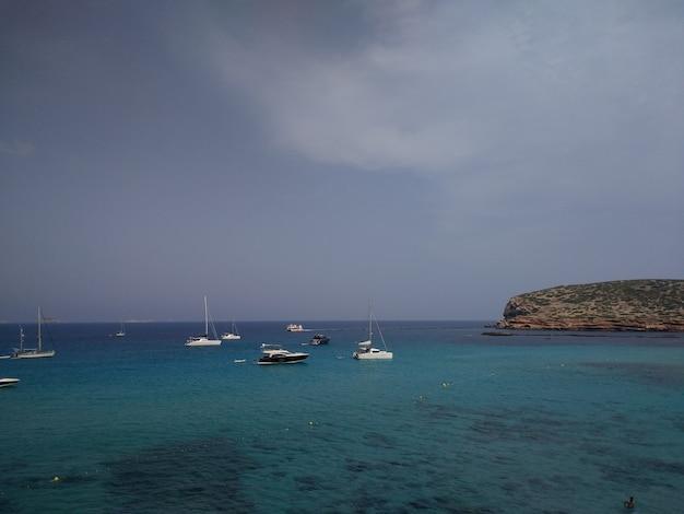 Küste neben ibiza mit ein paar booten vor dem stürmischen wetter