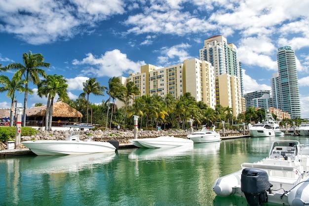 Küste von miami beach mit hotelgebäuden in der nähe der bucht mit weißen yachten und booten mit grünen palmen auf bewölktem hintergrund des blauen himmels