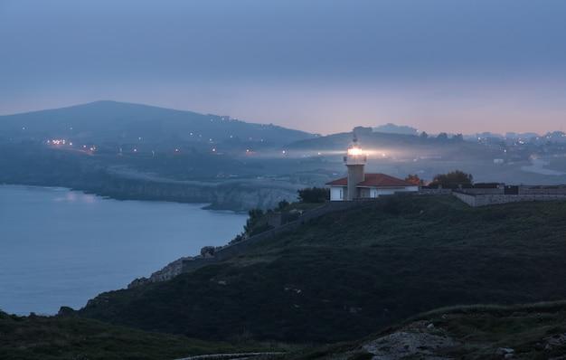 Küstenlandschaft mit einem leuchtturm bei sonnenaufgang