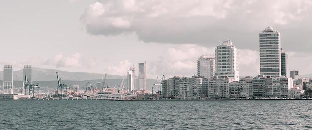 Küstenstadtbild mit modernen gebäuden unter bewölktem himmel. stadt izmir, türkei