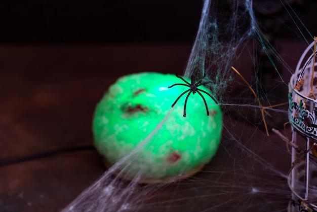 Kugel der grünen lampe der hexe mit kerzen und spinnennetzen auf einem schwarzen. halloween party