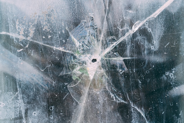 Kugel zerbrochenes fensterglas mit einem loch