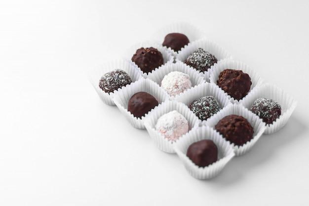 Kugelförmige pralinen verpackt in kleinen papierkörben lokalisiert auf weißem hintergrund. leckeres dessert. hausgemachte süße. minimaler stil.