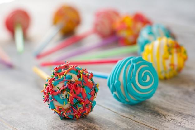 Kugelförmige süßigkeiten auf stöcken. bonbons mit glasur. frische cakepops. urlaubsstimmung und appetit.