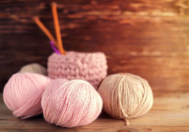 Kugeln aus rosa garn und stricknadeln auf einem hölzernen hintergrund.