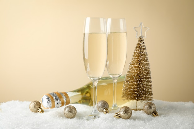 Kugeln, champagnergläser und flasche gegen beigen raum, platz für text