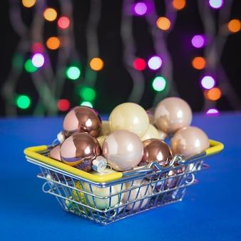 Kugeln für einen weihnachtsbaum in einem eisenkorb auf einer oberfläche der bunten lichter