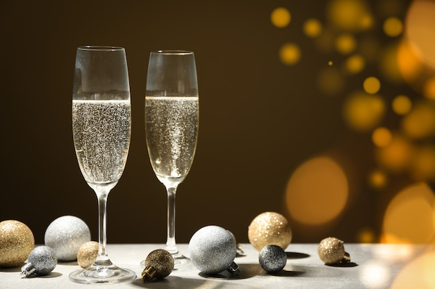 Kugeln und champagnergläser auf dekoriertem raum. bokeh-effekt
