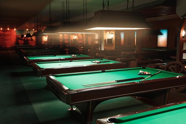 Kugeln und queues liegen keine tische in einem billardzimmer. grünes tuch.