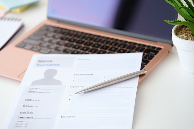 Kugelschreiber liegt auf lebenslaufdokument für beschäftigung in der nähe von laptop-nahaufnahme