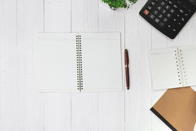 Kugelschreiber mit notizbuchpapier und taschenrechner auf holz