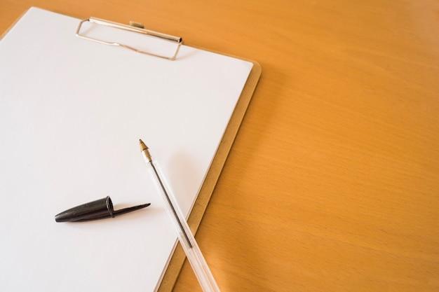 Kugelschreiber und klemmbrett mit papieren