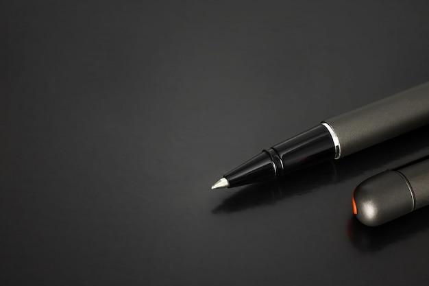Kugelschreiber und kugelschreiberkappe auf dunklem hintergrund mit luxusart.