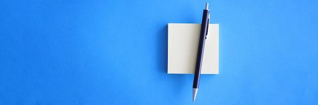 Kugelschreiber und papieraufkleber liegen auf blauem hintergrund nahaufnahme