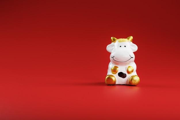 Kuhfigur auf rotem hintergrund, neujahrskonzept