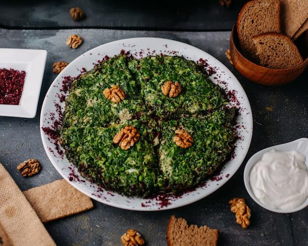 Kuku greenies mahlzeit bunt mit walnuss entworfen innerhalb weißer platte zusammen mit brotlaib joghurt auf grau