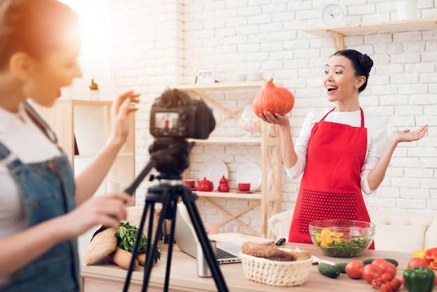 Kulinarische blogger halten kürbis mit einem mädchen hoch.