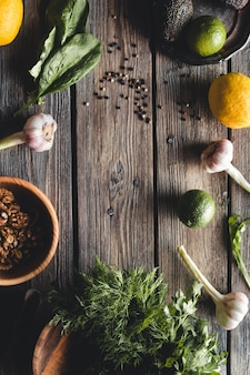 Kulinarische grüne kräuter, spinat, dill, petersilie, avocado in einer holzkiste lokalisiert auf weißem hintergrund