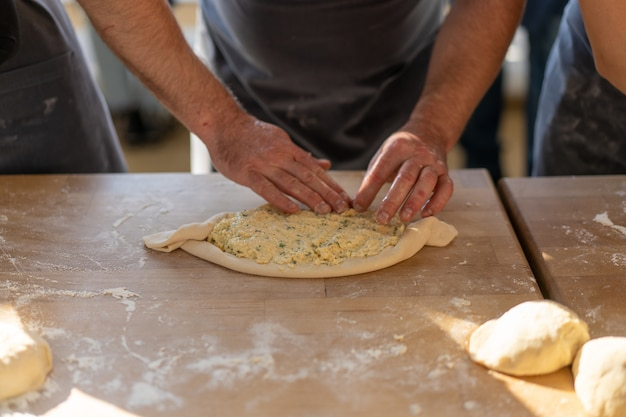 Kulinarische meisterklasse. nahaufnahme von den männlichen händen, die khachapuri zubereiten. traditionelles georgisches käsebrot. georgisches essen