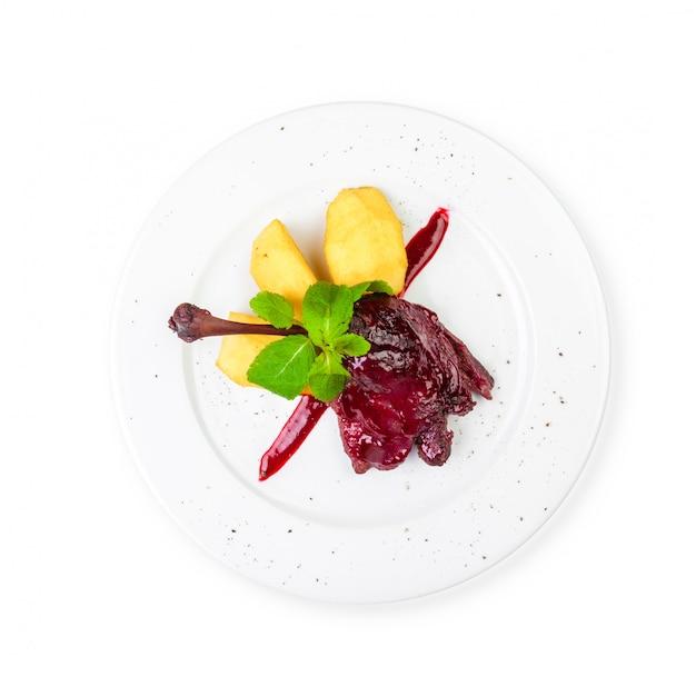 Kulinarischer entenbraten auf der platte lokalisiert auf weißem hintergrund.