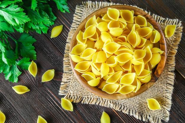 Kulinarischer hintergrund mit conchiglie-teigwaren auf holztisch. pasta in form von muscheln