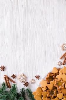 Kulinarischer hintergrund mit frisch gebackenem weihnachtslebkuchen, -gewürzen und -tannenzweigen. kopieren sie platz