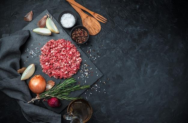 Kulinarischer hintergrund mit gehacktem frischem fleisch und zwiebeln auf einem schwarzen betonhintergrund.