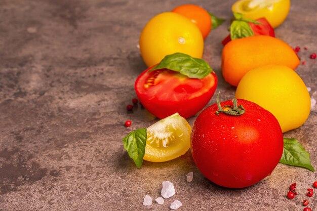 Kulinarischer hintergrund mit reifen tomaten und basilikumblättern. verschiedenes buntes gemüse, meersalz und rosa pfefferkörner auf dunklem steinbetonhintergrund, kopienraum
