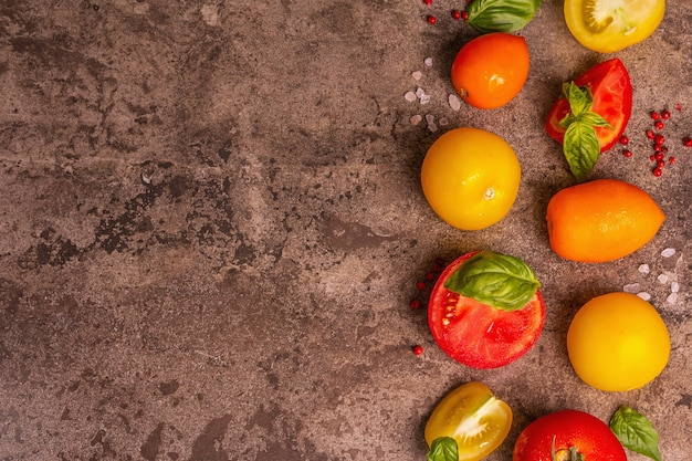 Kulinarischer hintergrund mit reifen tomaten und basilikumblättern. verschiedenes buntes gemüse, meersalz und rosa pfefferkörner auf einem dunklen steinbetonhintergrund, draufsicht