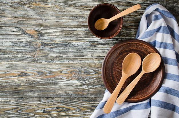 Kulinarischer hintergrund mit rustikalem küchengeschirr auf weinleseholztisch.