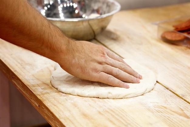 Kulinarischer koch, der tomatenpizza kocht
